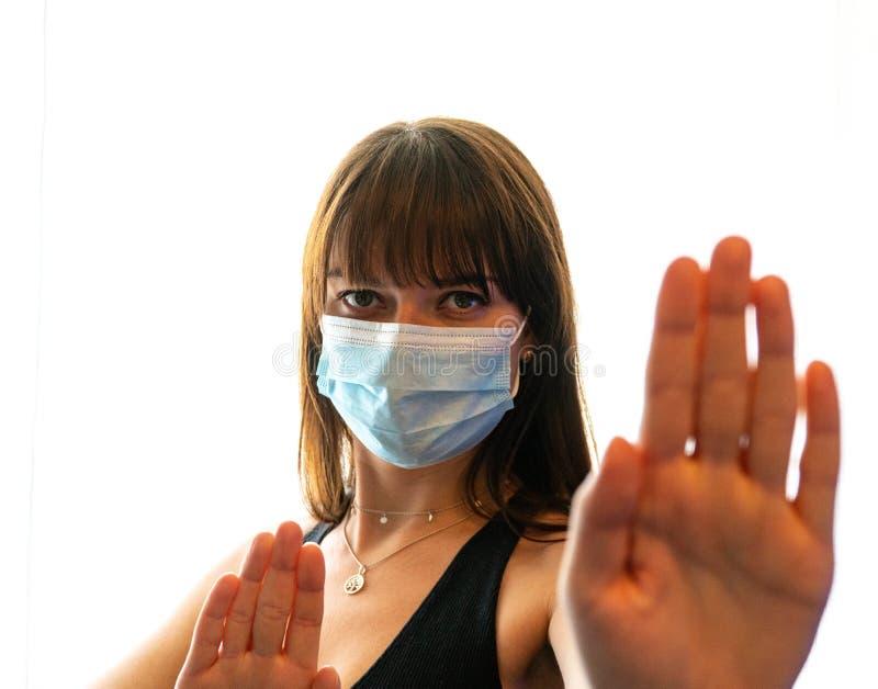 Молодая женщина, одетая в маску лица, жестикулирует, чтобы остановиться стоковое фото