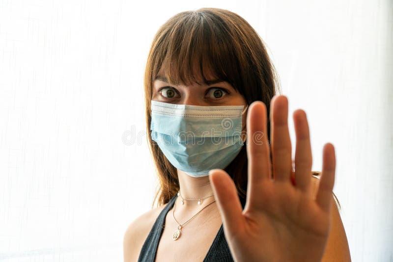 Молодая женщина, одетая в одноразовую маску лица, жестом останавливается стоковые изображения rf