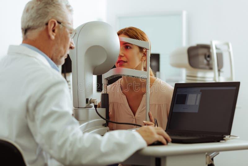 Молодая женщина опытного глазного врача рассматривая стоковые изображения rf