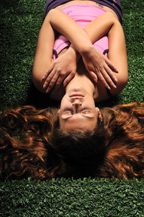 Молодая женщина ослабляет на зеленых лестницах стоковое фото