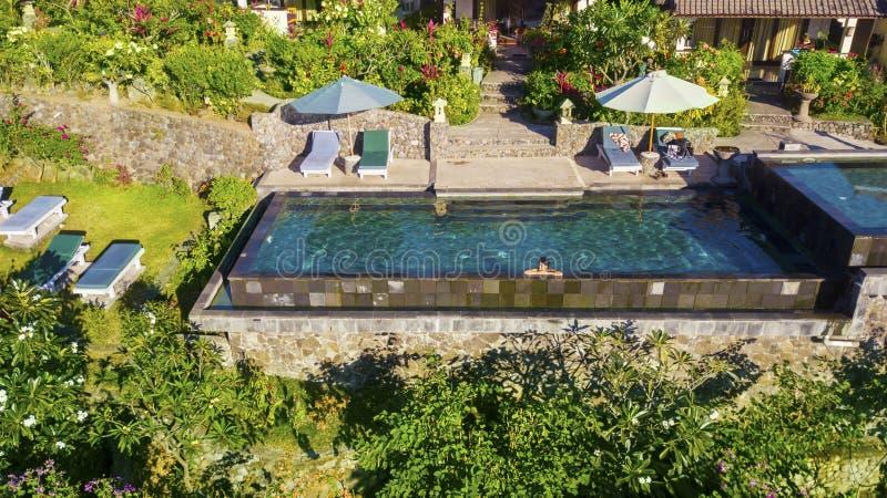 Молодая женщина ослабляя в роскошном бассейне заплыва стоковое фото rf