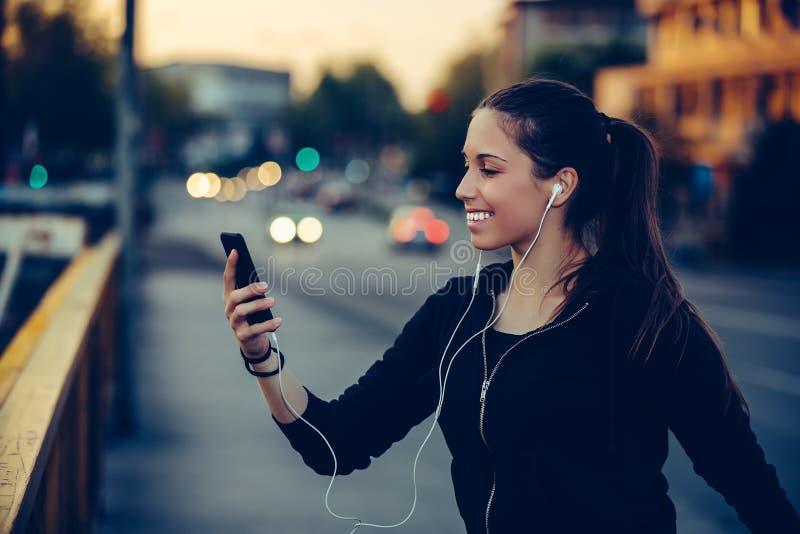 Молодая женщина ослабляя после jogging на мосте, вечером стоковое изображение rf