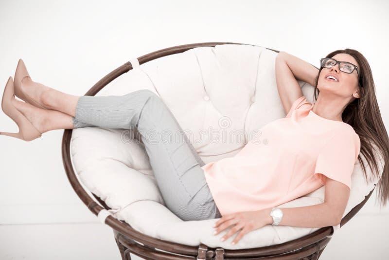 Молодая женщина отдыхая в удобном стуле стоковые фото