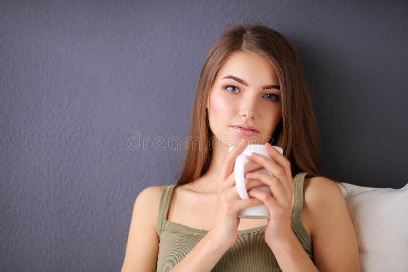 Молодая женщина отдыхая на кресле и выпивая чае в комнате стоковые фото
