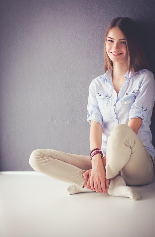 Молодая женщина отдыхая на кресле и выпивая чае в комнате стоковое изображение rf