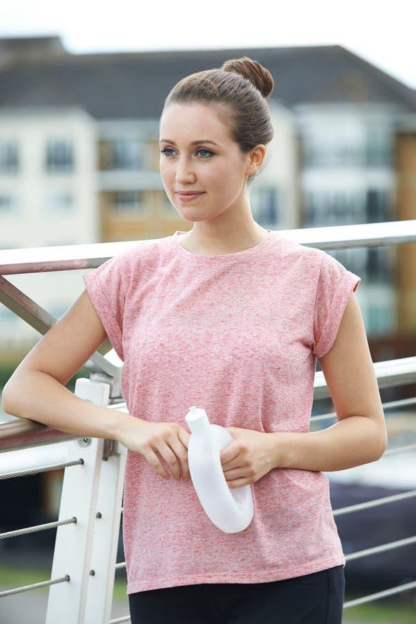 Молодая женщина отдыхая на мосте города во время тренировки стоковые изображения rf