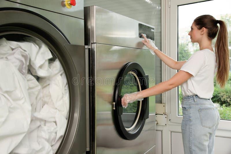 Молодая женщина отжимая кнопки на стиральной машине стоковые фотографии rf
