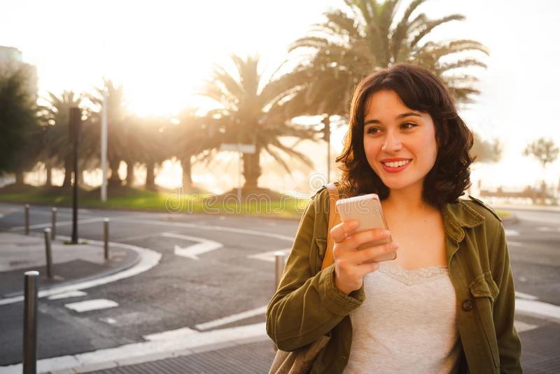 Молодая женщина отправляя сообщения голоса на улице стоковое изображение rf