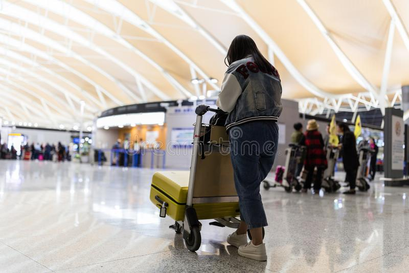 Молодая женщина от за транспортировать багаж от стоянки прибытия к терминалу отклонения международного аэропорта вагонеткой багаж стоковые изображения