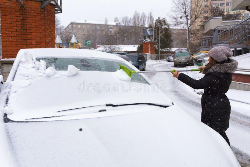 Молодая женщина очищает снег от поверхности ее автомобиля стоковое фото