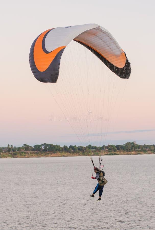 Молодая женщина парашютируя вниз к земному берегу реки стоковые изображения
