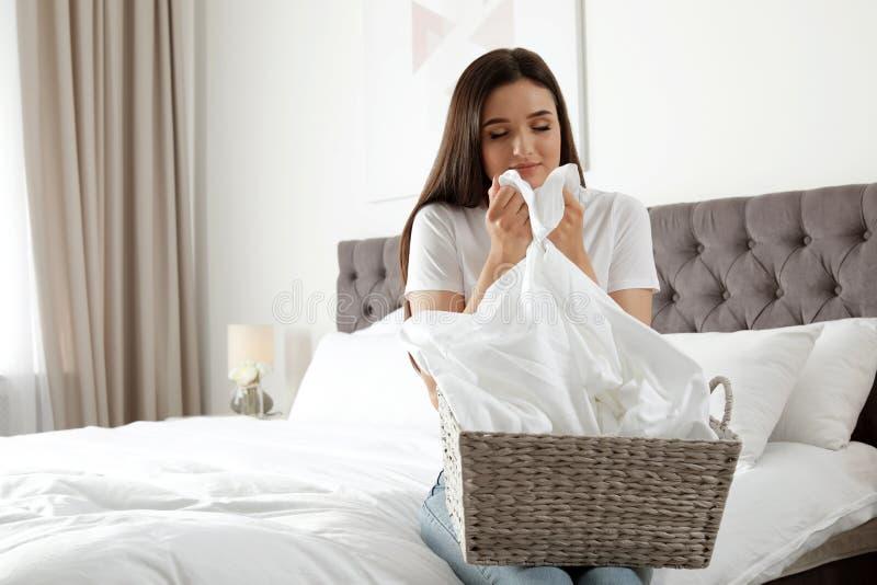 Молодая женщина пахнуть свежей прачечной в спальне стоковое фото