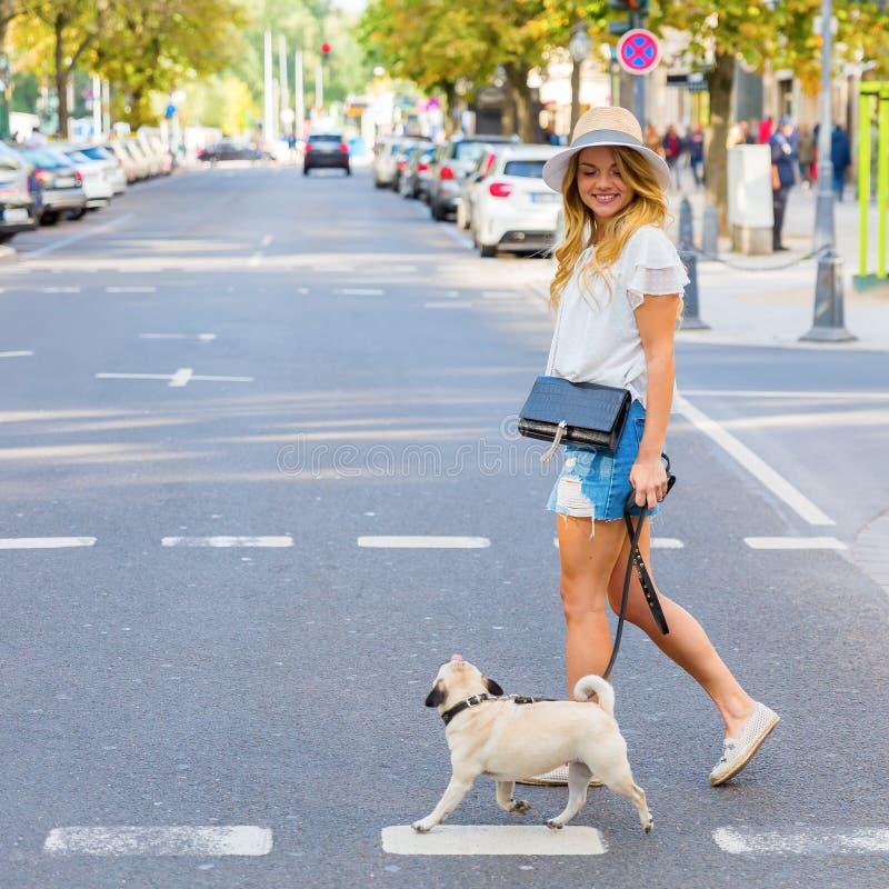 Молодая женщина пересекает острословие улицы города мопс стоковая фотография rf
