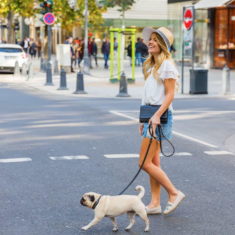 Молодая женщина пересекает острословие улицы города мопс стоковые фото