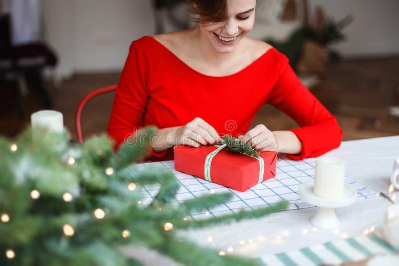Молодая женщина подготавливает подарки на приходя зимние отдыхи стоковое изображение