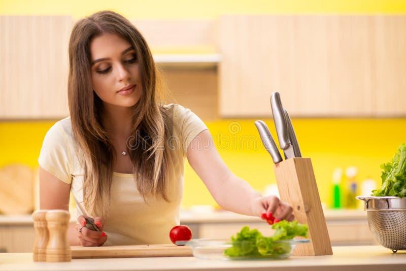 Молодая женщина подготавливая салат дома в кухне стоковое изображение