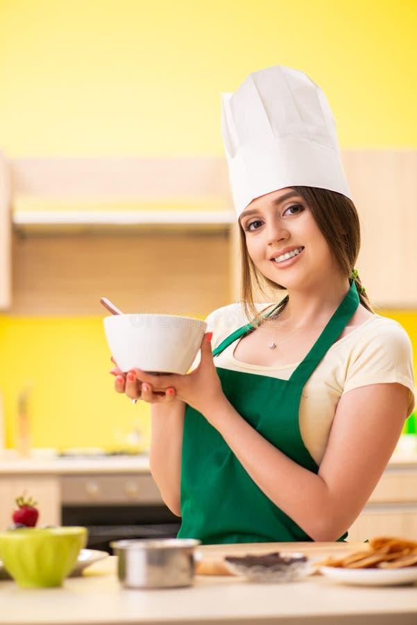Молодая женщина подготавливая салат дома в кухне стоковое изображение rf