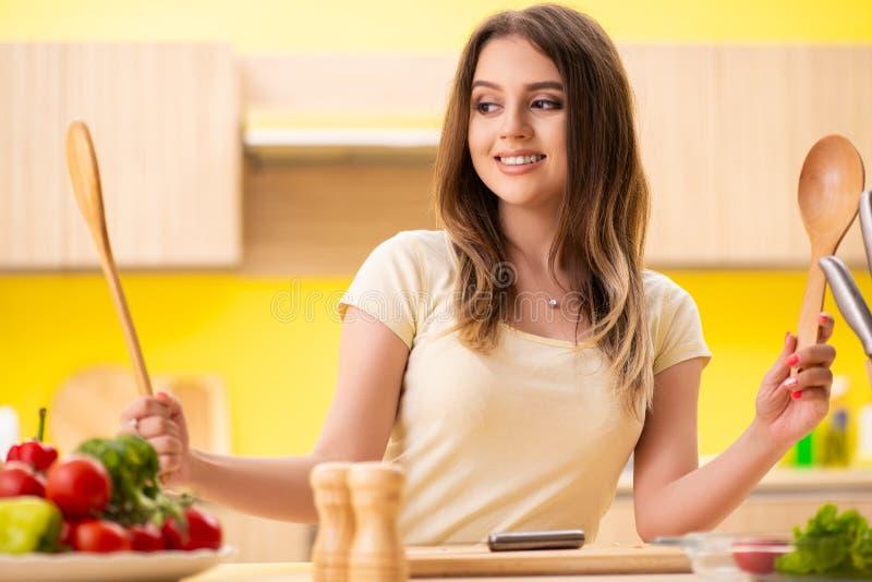 Молодая женщина подготавливая салат дома в кухне стоковые изображения rf