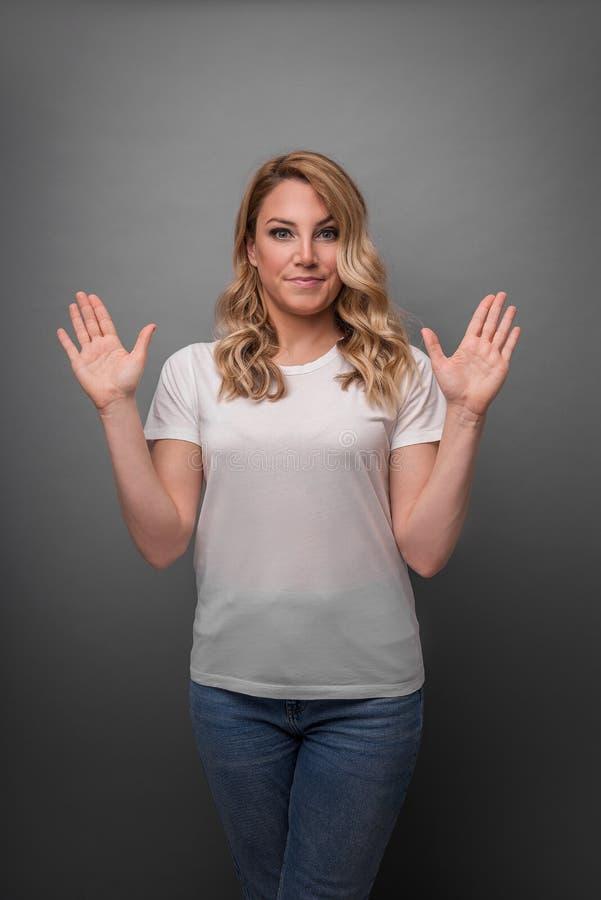 Молодая женщина поднимает ее руки вверх по показывать сюрприз или запирательство стоковое фото rf
