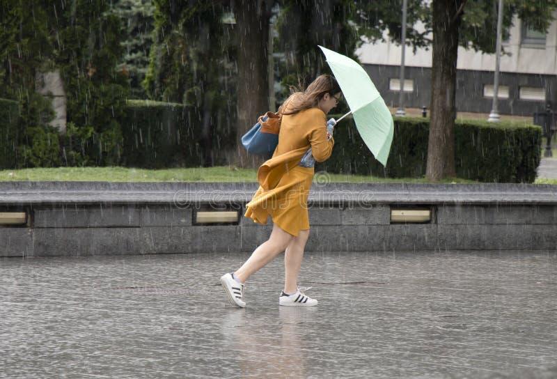 Молодая женщина под зонтиком во время неожиданного ливня весны стоковое изображение rf