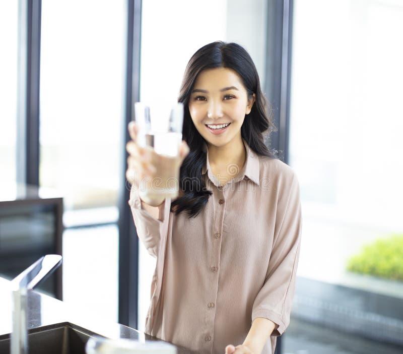 Молодая женщина показывая выпивая стекло с водой в кухне стоковое изображение