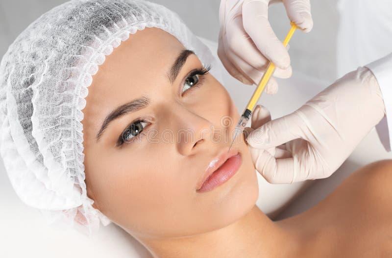 Молодая женщина получая впрыску губ в клинике стоковые изображения rf