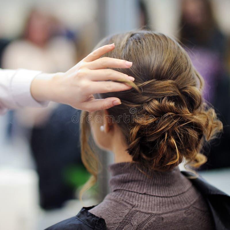 Молодая женщина получая ей волосы сделанный перед партией стоковая фотография rf