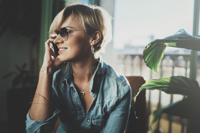Молодая женщина портрета усмехаясь нося вскользь одежды и говоря на приборе smartphone пока тратящ ослабьте время внутри стоковое изображение rf