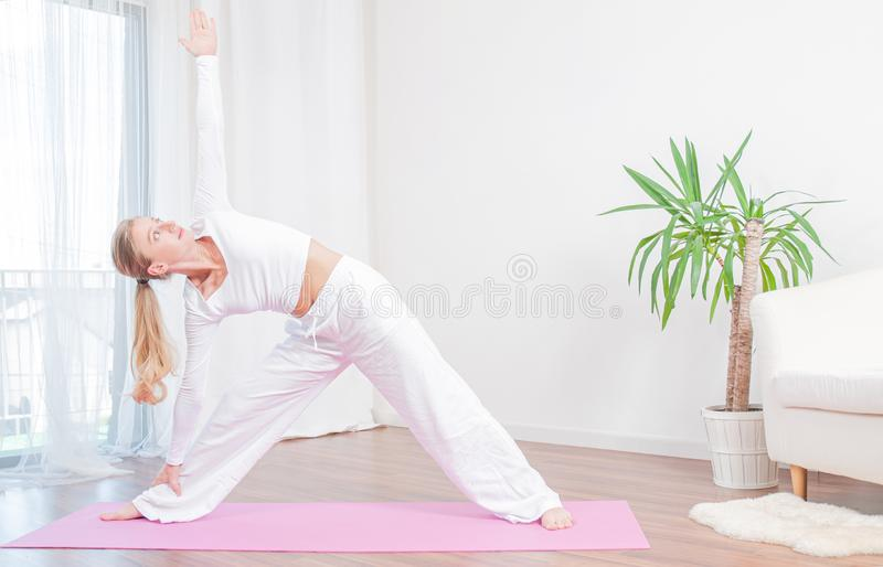 Молодая женщина практикует йогу дома на циновке, девушке делая тренировку Utthita Trikonasana, выдвинутое представление треугольн стоковые фото