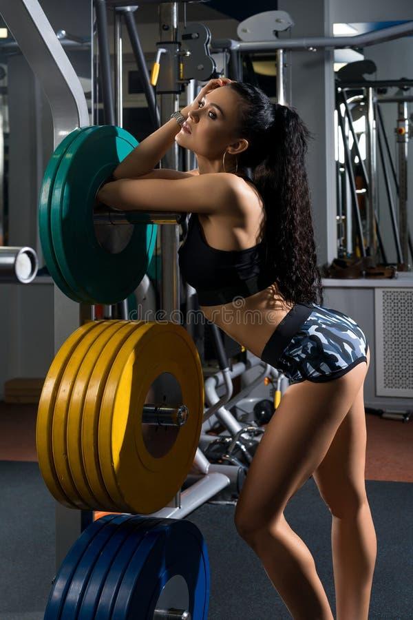 Молодая женщина представляя с плитами весов стоковые фото