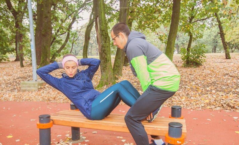 Молодая женщина пригонки делая тренировку фитнеса Сидеть-поднимает на открытом воздухе разминку стоковое изображение