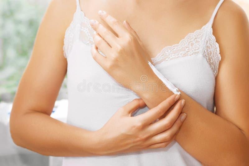 Молодая женщина прикладывает сливк на ее руках Фокус на руках Лосьон Красивые руки женщины Мягкая кожа, концепция skincare Автомо стоковое фото