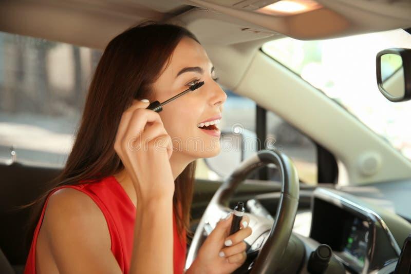 Молодая женщина прикладывая макияж на месте водителя автомобиля стоковые фото