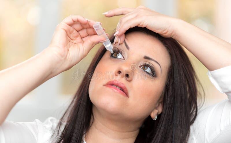 Молодая женщина прикладывая eyedrops стоковые фото
