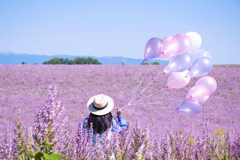Молодая женщина принимает воздушный шар и перемещение на поле цветка в Valensole, Франции во время лета стоковое фото rf