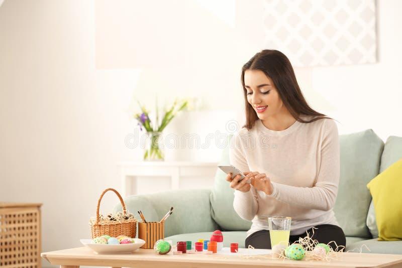 Молодая женщина принимая фото покрашенных пасхальных яя дома стоковая фотография rf