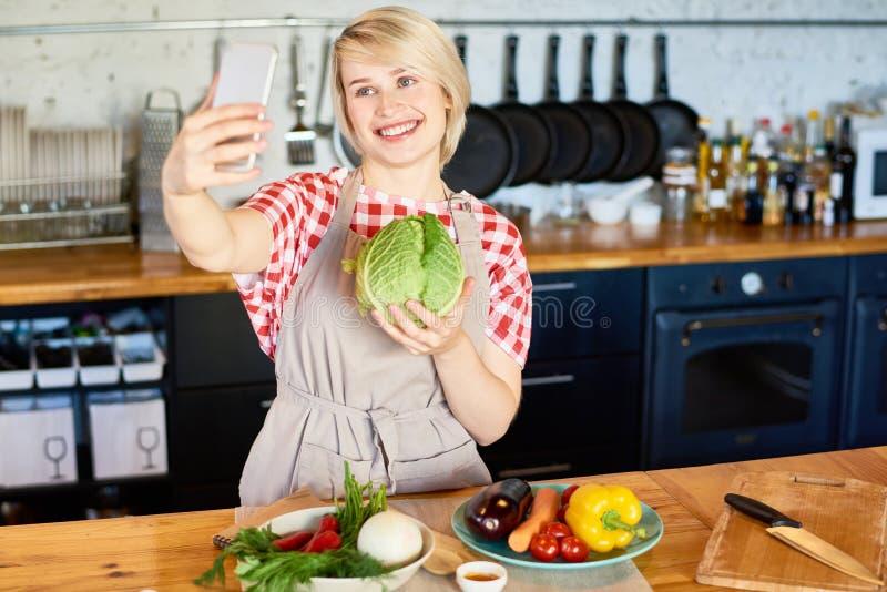 Молодая женщина принимая Selfie в кухне стоковое фото rf