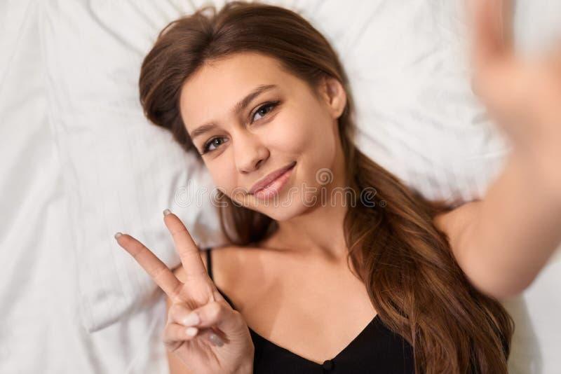 Молодая женщина принимая selfie на кровати стоковое фото rf
