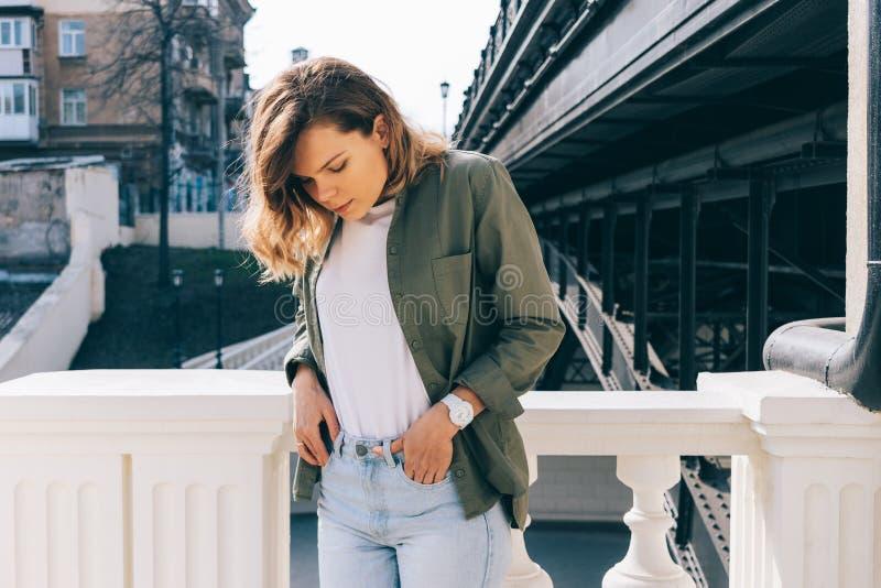 Молодая женщина при волнистые волосы стоя рядом с мостом стоковая фотография rf