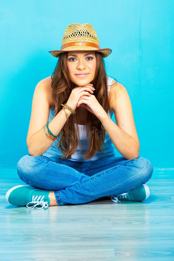 Молодая женщина при длинное вьющиеся волосы сидя на floo стоковое фото