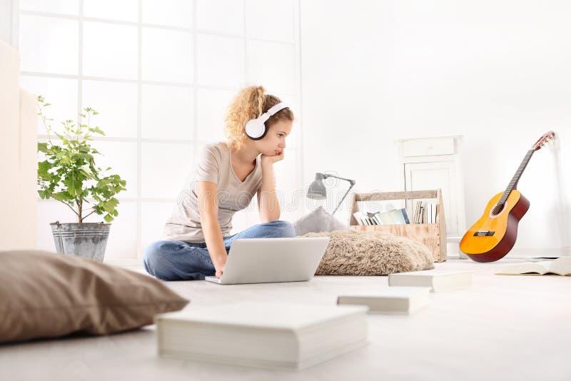 Молодая женщина при компьютер, наушники, гитара и книги, сидя стоковые изображения rf