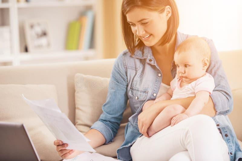 Молодая женщина при младенец работая дома с компьтер-книжкой стоковое фото