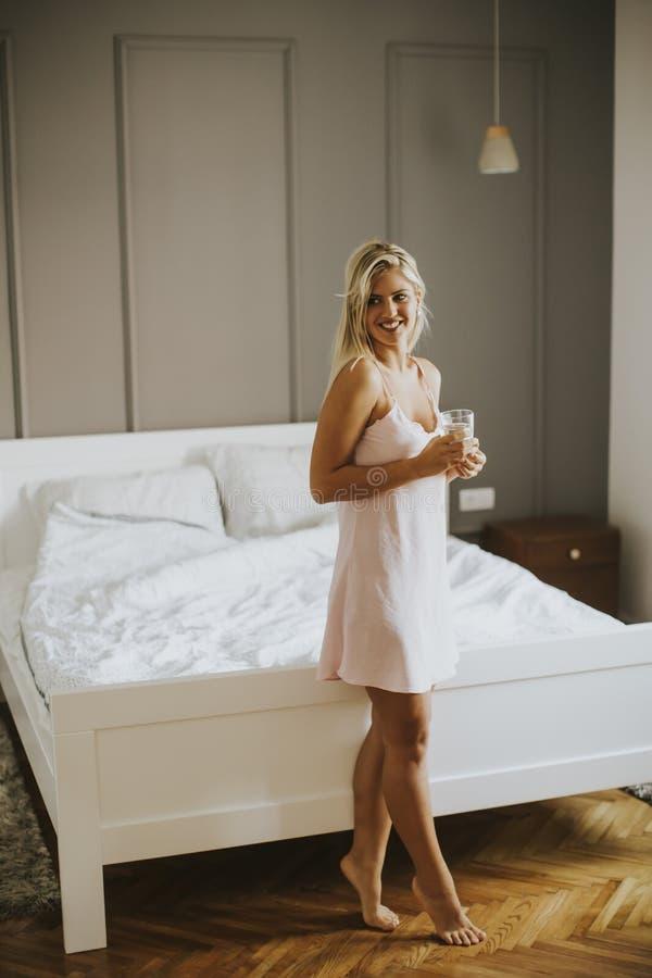 Молодая женщина при стекло воды представляя в спальне стоковое фото rf