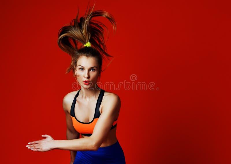 Молодая женщина при тело пригонки скача и бежать против серой предпосылки стоковое фото