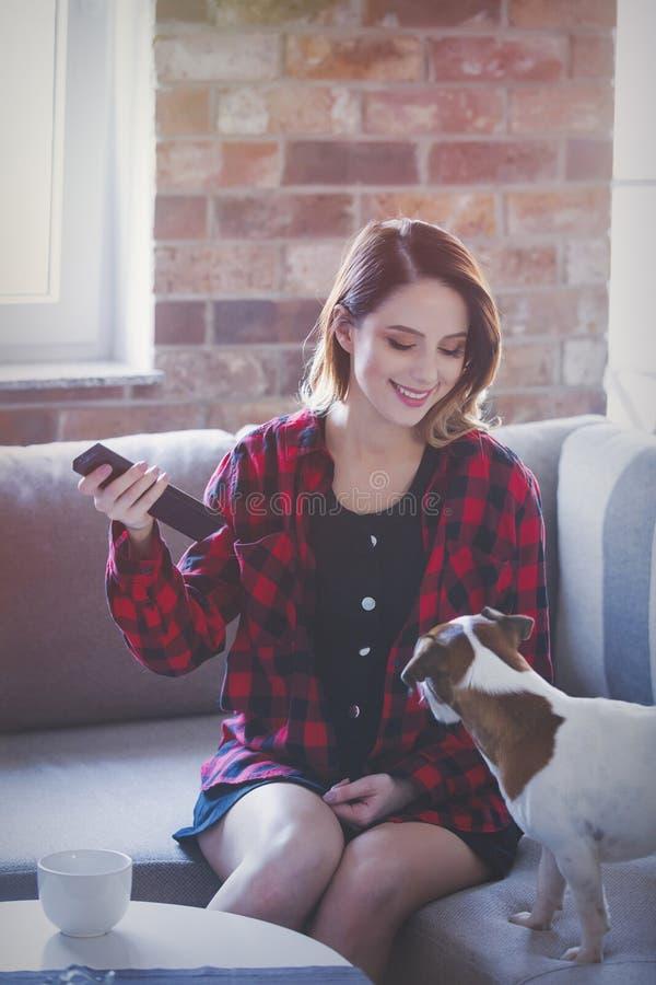 Молодая женщина при чашка чаю или кофе сидя на софе стоковое фото