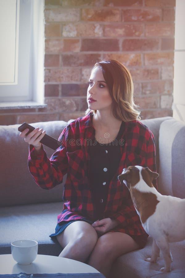 Молодая женщина при чашка чаю или кофе сидя на софе стоковые изображения rf