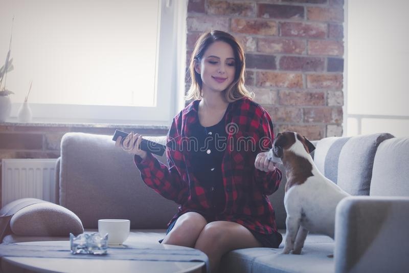 Молодая женщина при чашка чаю или кофе сидя на софе стоковое изображение rf