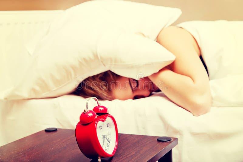 Молодая женщина пробуя спать когда звенеть будильника стоковые изображения