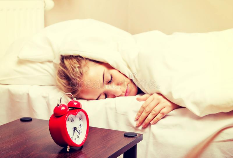 Молодая женщина пробуя спать когда звенеть будильника стоковые фото