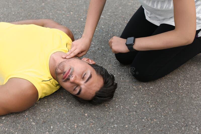 Молодая женщина проверяя ИМП ульс обморочного человека стоковое изображение rf